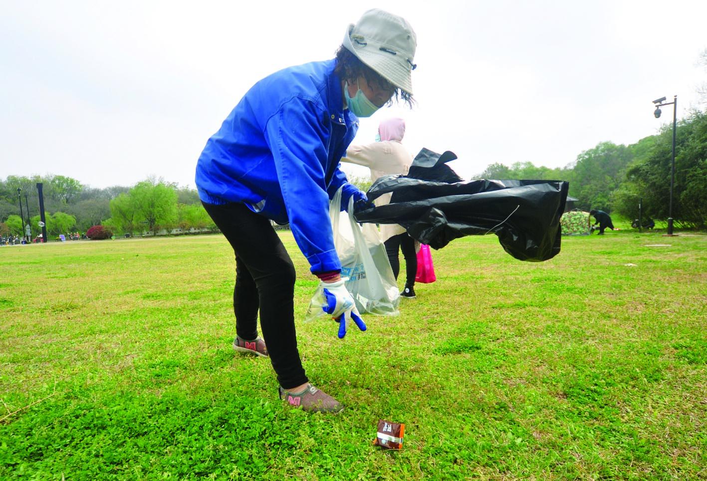 草坪上的环卫工,每天捡垃圾一吨